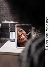 Cute dark-skinned woman with coral lipstick smiling positively