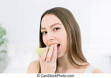 Beautiful smile, white strong teeth. Head and shoulders of young woman with snow-white smile holding green apple, teethcare.
