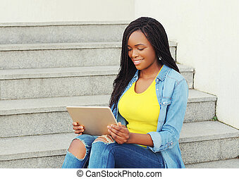 Beautiful smiling african woman using tablet pc computer in city