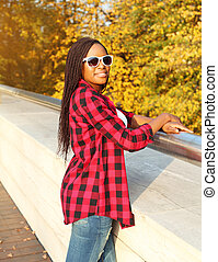 Beautiful smiling african woman wearing a sunglasses, red checkered shirt in sunny autumn day