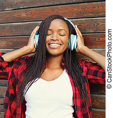 Beautiful smiling african woman with headphones enjoying listens to music in city
