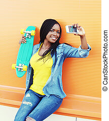 Beautiful smiling african woman with skateboard taking self portrait on smartphone over yellow background