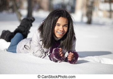 Beautiful smiling american black female lying in the snow...