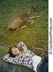 Beautiful smiling Asian woman lying down and emulate deer..