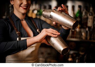 Beautiful smiling barmaid making cocktail in shaker