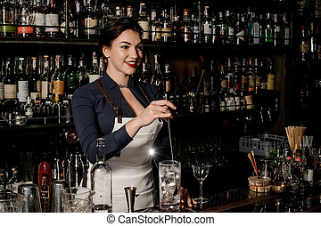 Beautiful smiling barman woman stirring fresh summer drink...