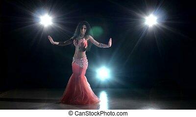 Beautiful, smiling belly dancer girl dancing exotic dance movement on black, back light