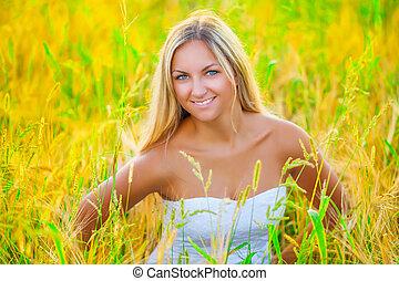 beautiful smiling blonde on wheat field