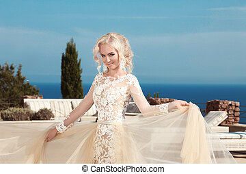 Beautiful smiling bride dressed in elegance white wedding dress over sea and blue sky