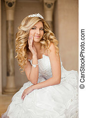 Beautiful smiling bride woman with long curly hair posing in wedding dress at interior. Beauty indoor portrait.