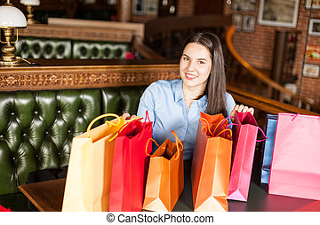 Beautiful smiling brunette girl shows lot of shopping bags she has sitting in a coffee shop