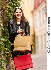 Beautiful smiling brunette girl shows shopping bags after visiting boutique store