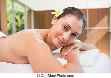 Beautiful smiling brunette lying on massage table with salt scru