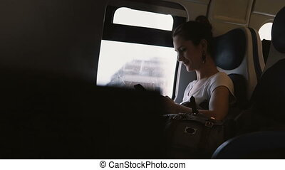 Beautiful smiling European girl sending messages to friends using smartphone messenger app traveling on the train.