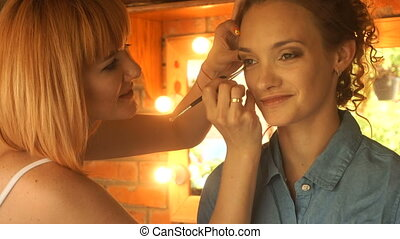 beautiful smiling girl and a makeup artist make-up