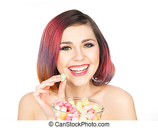 Beautiful smiling girl eating sweets from a bowl.