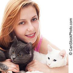 beautiful smiling girl hugging her two cats