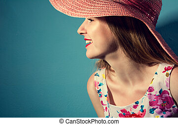 Beautiful smiling girl in a hat in profile