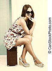 Beautiful smiling girl in a summer dress sits on a suitcase