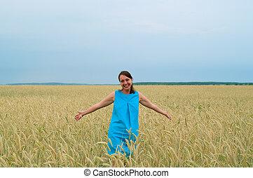 smiling girl in blue dress in field