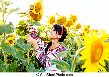 Beautiful smiling girl in embrodery holding a sunflower on a field