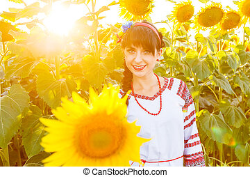 Beautiful smiling girl in embrodery on a sunflower field
