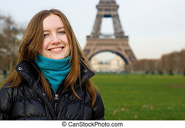 Beautiful smiling girl in Paris near the Eiffel Tower