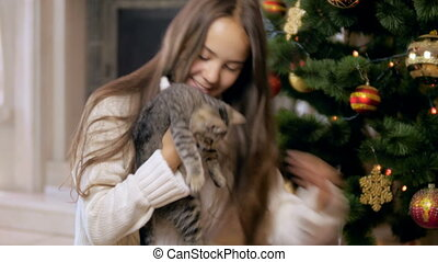 Beautiful smiling girl in sweater holding and caressing little kitten in living room decroated for Christmas