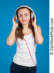 beautiful smiling girl listening music wearing white headphones in the studio over blue background