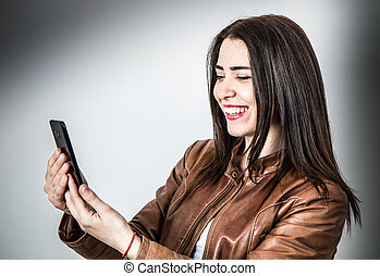 beautiful smiling girl look at the mobile phone
