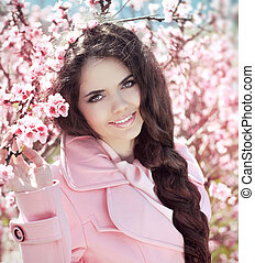 Beautiful smiling girl over pink blossom tree, outdoors ...