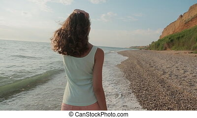 Beautiful smiling girl quickly walking on the sea water along the seashore in summer