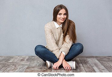 Beautiful smiling girl sitting on the floor with legs crossed