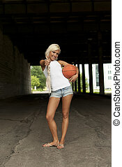 beautiful smiling girl standing with a basketball in the...