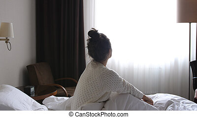 Beautiful smiling girl wakes up in bed in the morning sits in bed and looks at window