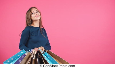 Beautiful smiling girl with a lot of shopping bags.