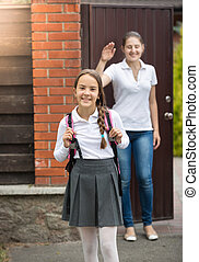 Beautiful smiling girl with bag going to school