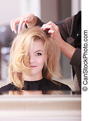 Beautiful smiling girl with blond wavy hair by hairdresser. Hairstylist with comb combing female client young woman in hairdressing beauty salon. Hairstyle.