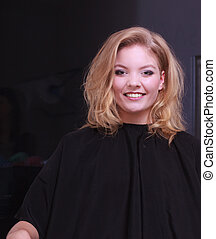 Beautiful smiling girl with blond wavy hair by hairdresser. Happy young woman in hairdressing beauty salon. Hairstyle.