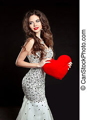 Beautiful smiling girl with red heart in luxury dress isolated on black background. Elegant brunette woman model with long wavy hair style, makeup.