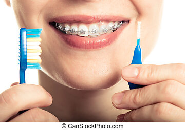 Beautiful smiling girl with retainer for teeth brushing teeth.