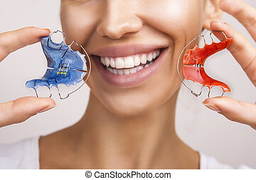 Dental and Ortho - Beautiful Smiling Girl Holding Retainer for Teeth (Braces for Teeth). Stomatology Orthodontics Dental Theme, Methods of Teeth (Bite) Correction and fix. White Smile Close-up.