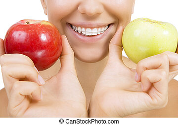 Beautiful smiling girl with retainer for teeth - healthy teeth and apples (Close Up, Isolated on white)