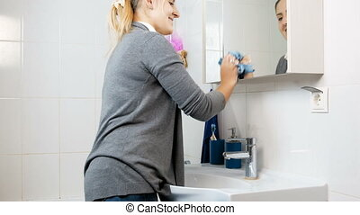 Beautiful smiling housewife cleaning mirror in bathroom