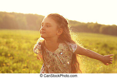Beautiful smiling kid girl trying to fly with happy look on nature bright sunset summer background. Closeup portrait