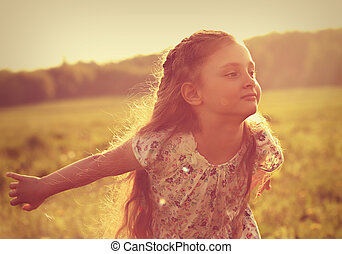 Beautiful smiling kid girl trying to fly with happy look on nature bright sunset summer background. Closeup toned portrait