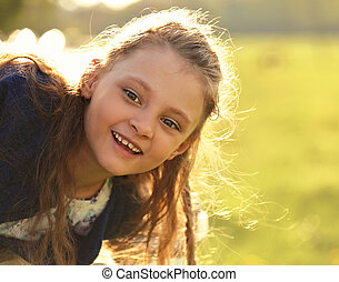 Beautiful smiling kid girl with happy look on nature bright summer green tree background. Closeup portrait