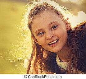 Beautiful smiling kid girl with happy look on nature summer green tree background. Closeup toned bright portrait