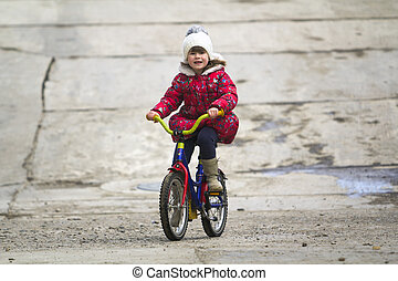 beautiful smiling little girl riding bicycle in a park