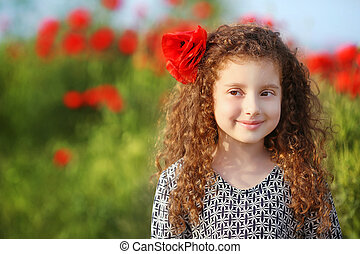 Beautiful smiling little girl with curly hair in poppies field at sunset. outdoor portrait